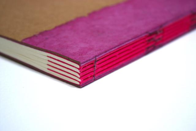 notitieboek met rugnaaisel in het zicht, kruissteek, open rug, kraft, katernen, meegenaaide platten